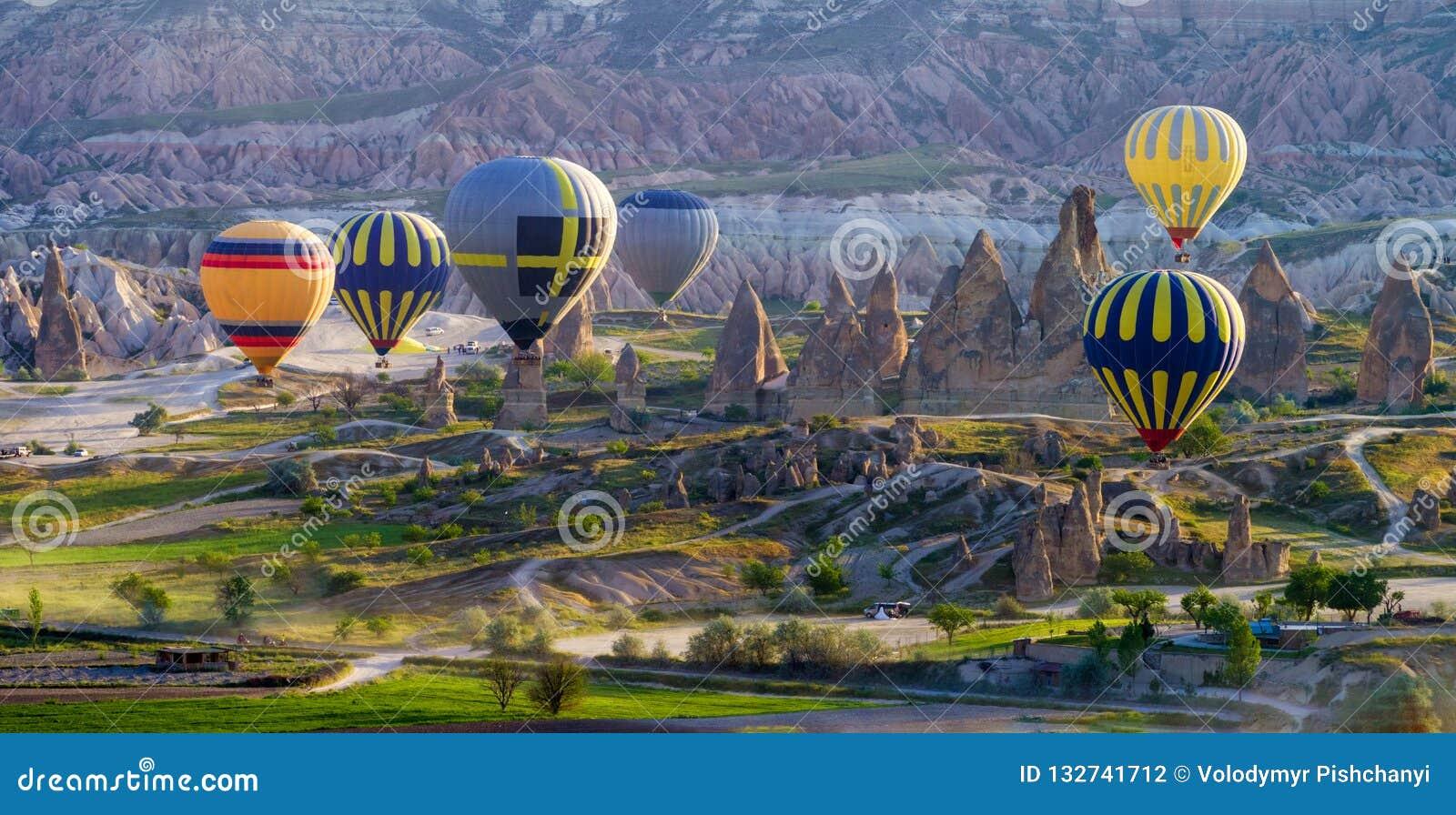 Πολύχρωμα μπαλόνια ζεστού αέρα στην ανατολή που πετούν πέρα από Cappadocia, Goreme,