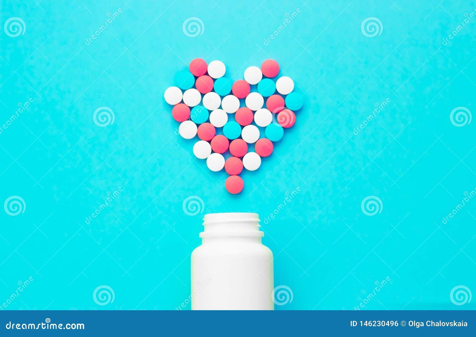 Πολύχρωμα χάπια από τα άσπρα βάζα σε ένα μπλε υπόβαθρο