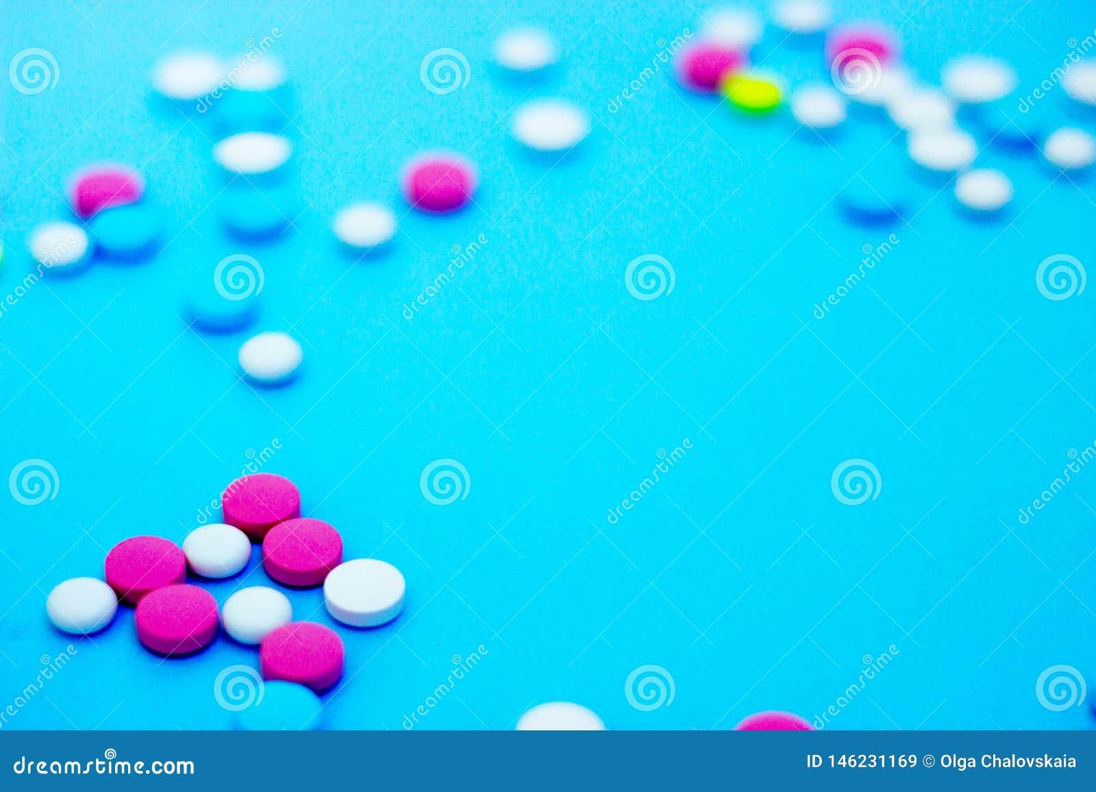 Πολύχρωμα χάπια στο μπλε υπόβαθρο με το διάστημα αντιγράφων