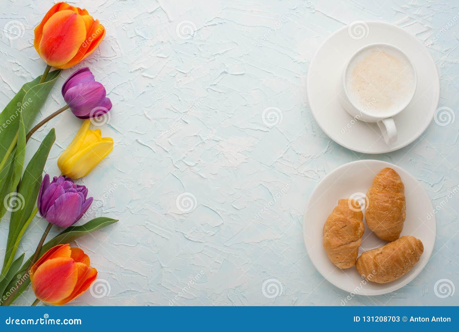 Πολύχρωμες τουλίπες με τον καφέ και croissants το ελαφρύ υπόβαθρο, τοπ άποψη, με το κενό διάστημα για το γράψιμο ή τη διαφήμιση