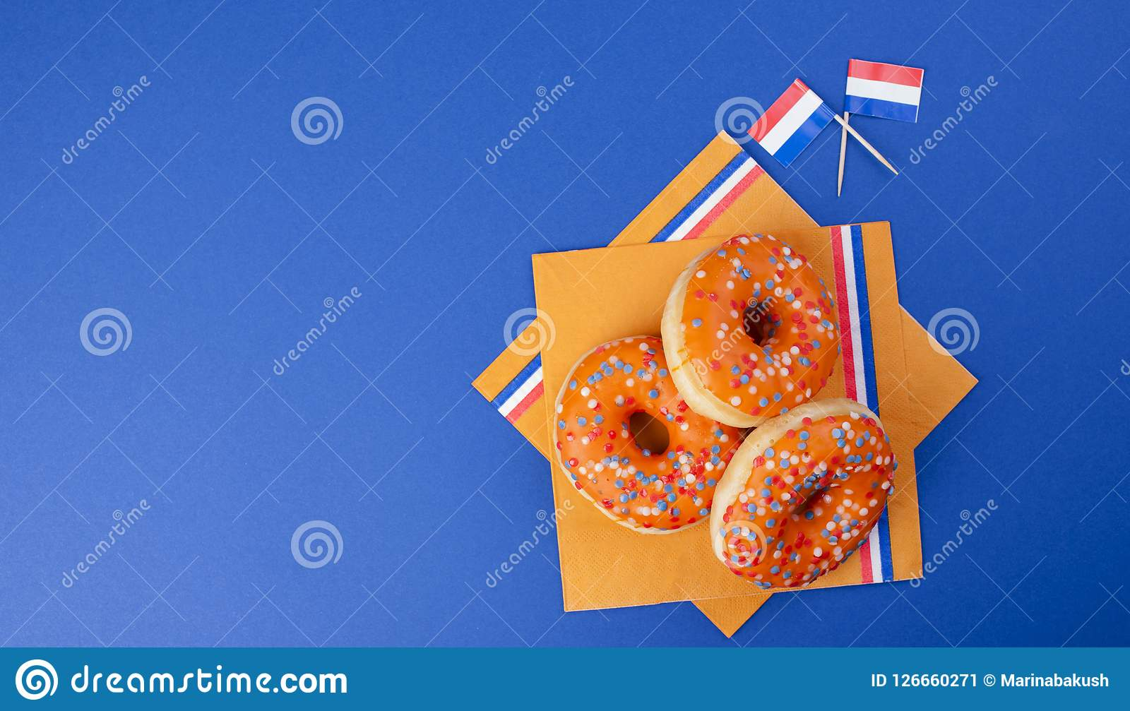 Πορτοκάλι donuts για την ημέρα βασιλιάδων ` s διακοπών, διακοπές της Ολλανδίας Ψήσιμο σε ένα μπλε υπόβαθρο Τοπ όψη διάστημα αντιγ