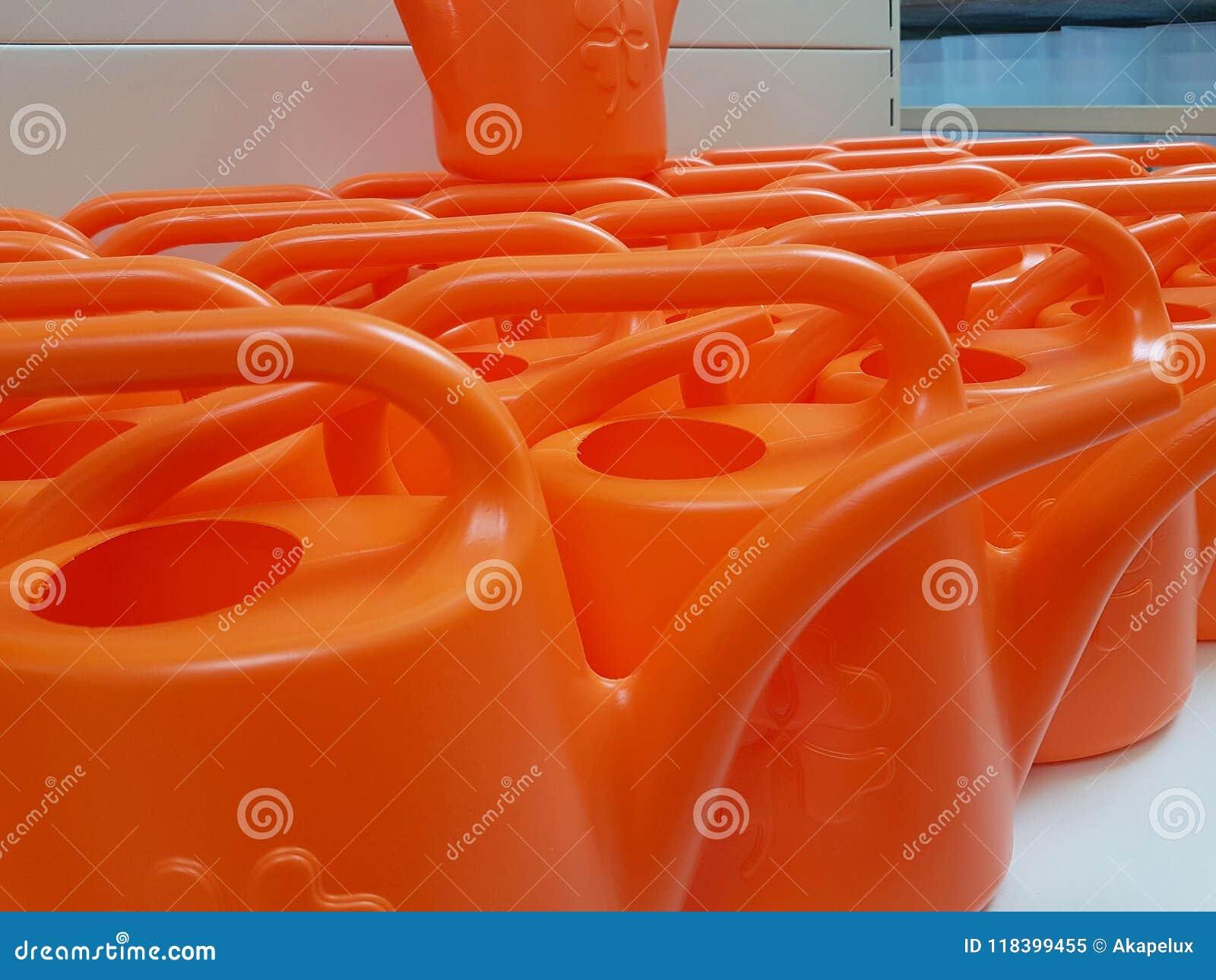 Πορτοκαλιά πλαστικά δοχεία ποτίσματος για να εμποτίσει τις εγκαταστάσεις Όργανα της εργασίας για τη γεωργία και την ερωτοτροπία γ