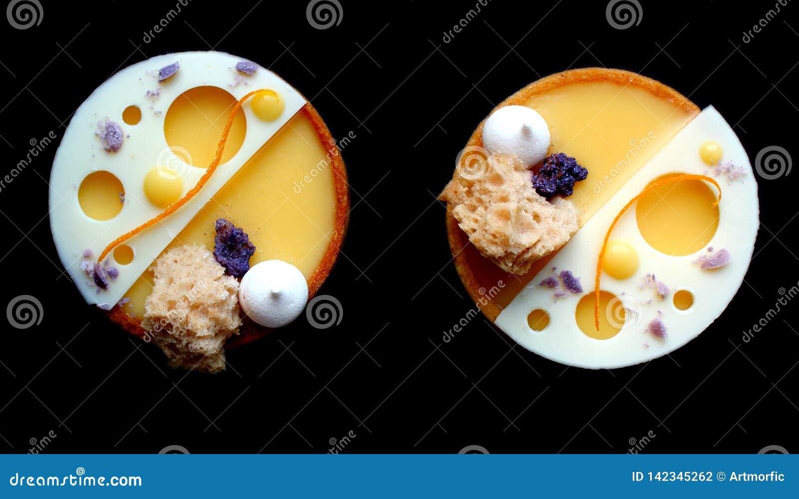 Πορτοκαλιά tarts με τις μαρέγκες και άσπρη σοκολάτα στο μαύρο υπόβαθρο