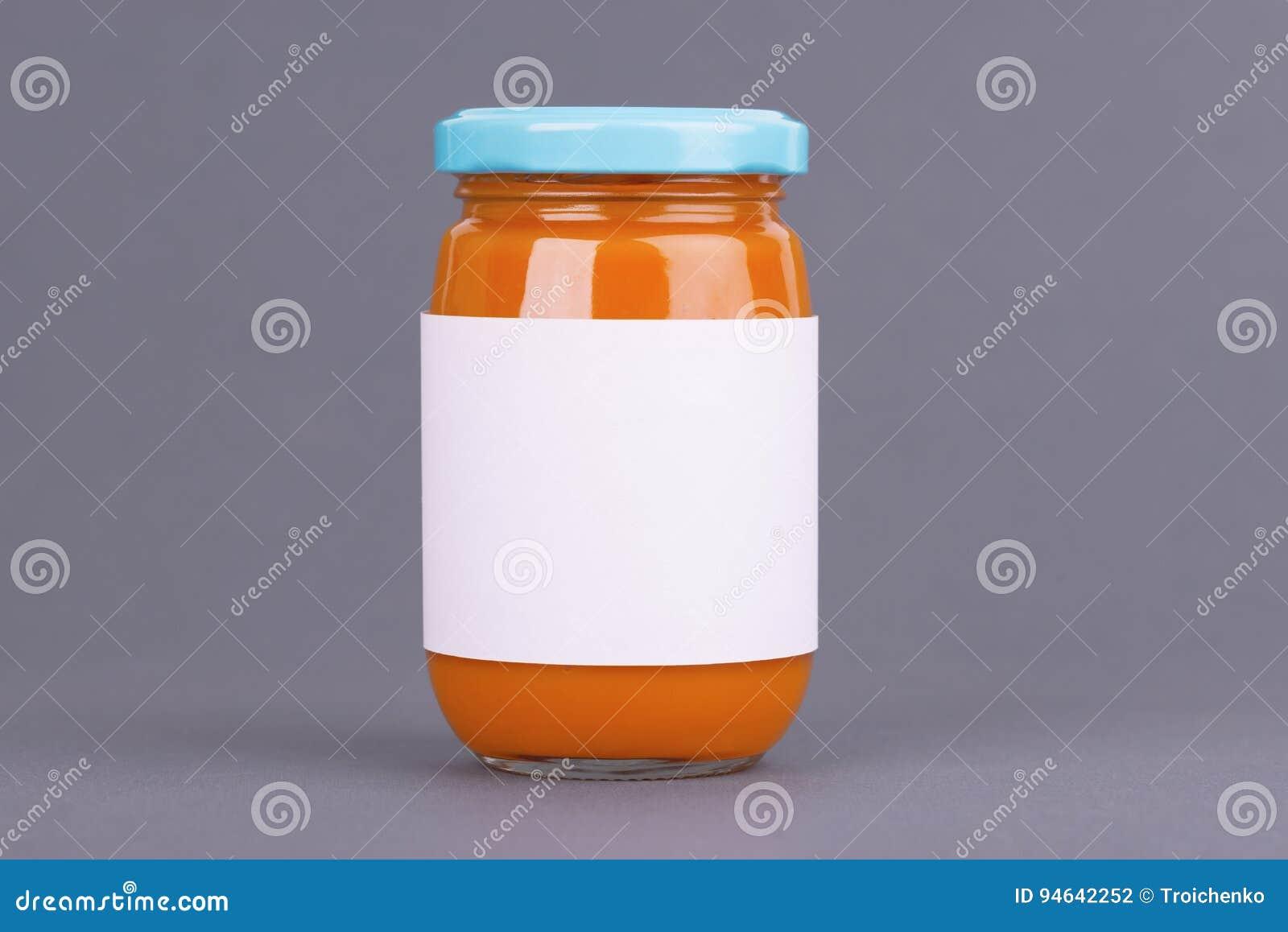 Πορτοκαλί βάζο γυαλιού για την τράπεζα παιδικών τροφών στο γκρίζο υπόβαθρο Οργανικός πουρές παιδικών τροφών Χλεύη επάνω χωρίς ετι