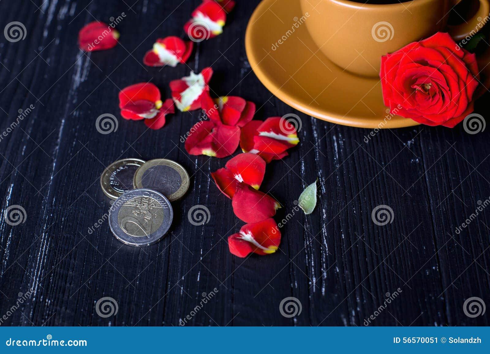 Download Πορτοκαλί φλυτζάνι καφέ με τα ροδαλά πέταλα και τα ευρο- νομίσματα στο μαύρο υπόβαθρο Στοκ Εικόνα - εικόνα από κούπα, λουλούδι: 56570051