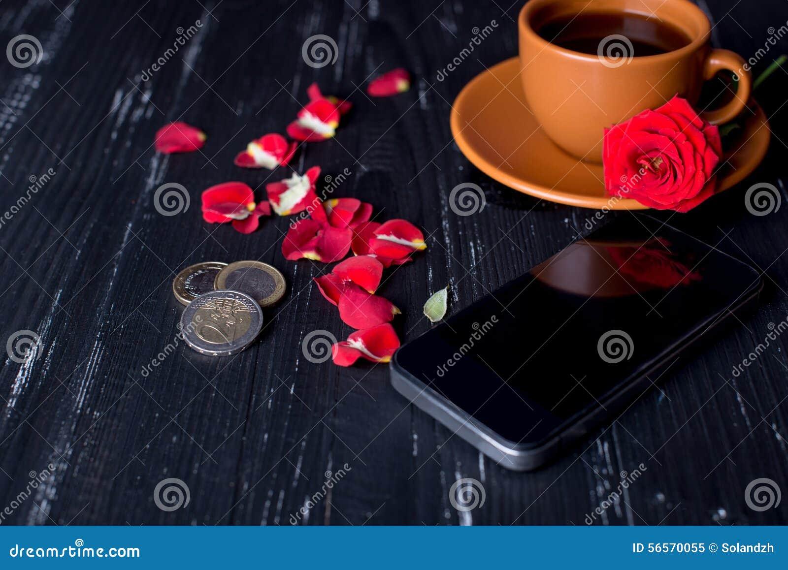 Download Πορτοκαλί φλυτζάνι καφέ με τα ροδαλά πέταλα, το κινητό τηλέφωνο και τα ευρο- νομίσματα στο μαύρο υπόβαθρο Στοκ Εικόνα - εικόνα από μαύρα, τρόφιμα: 56570055