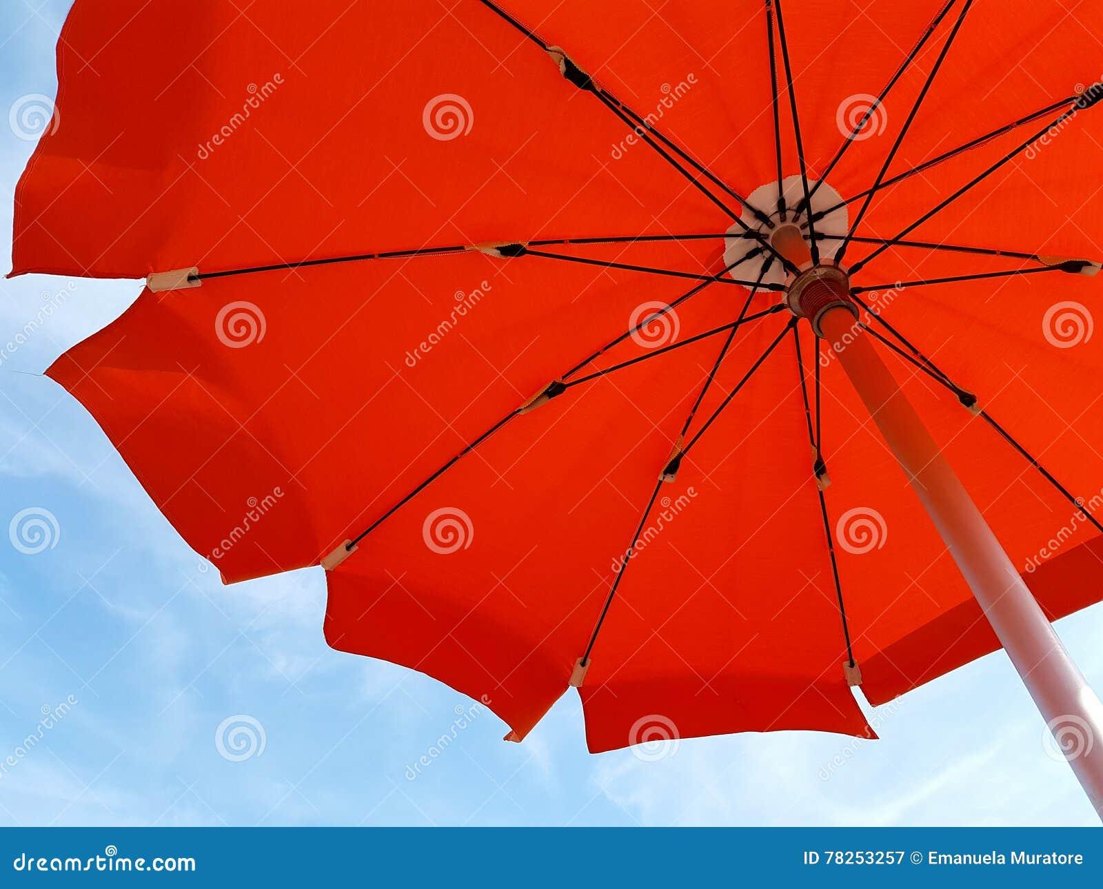 Πορτοκαλιά ομπρέλα παραλιών στον αέρα