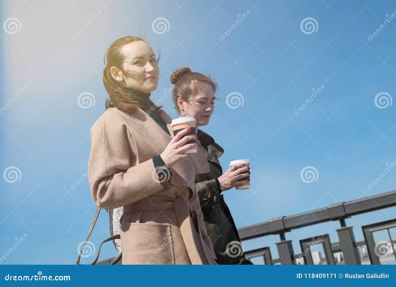 Πορτρέτο δύο νέων γυναικών στα μοντέρνα παλτά και με τα φλιτζάνια του καφέ για να πάρει μαζί, χαμηλότερη γωνία, παπαράτσι