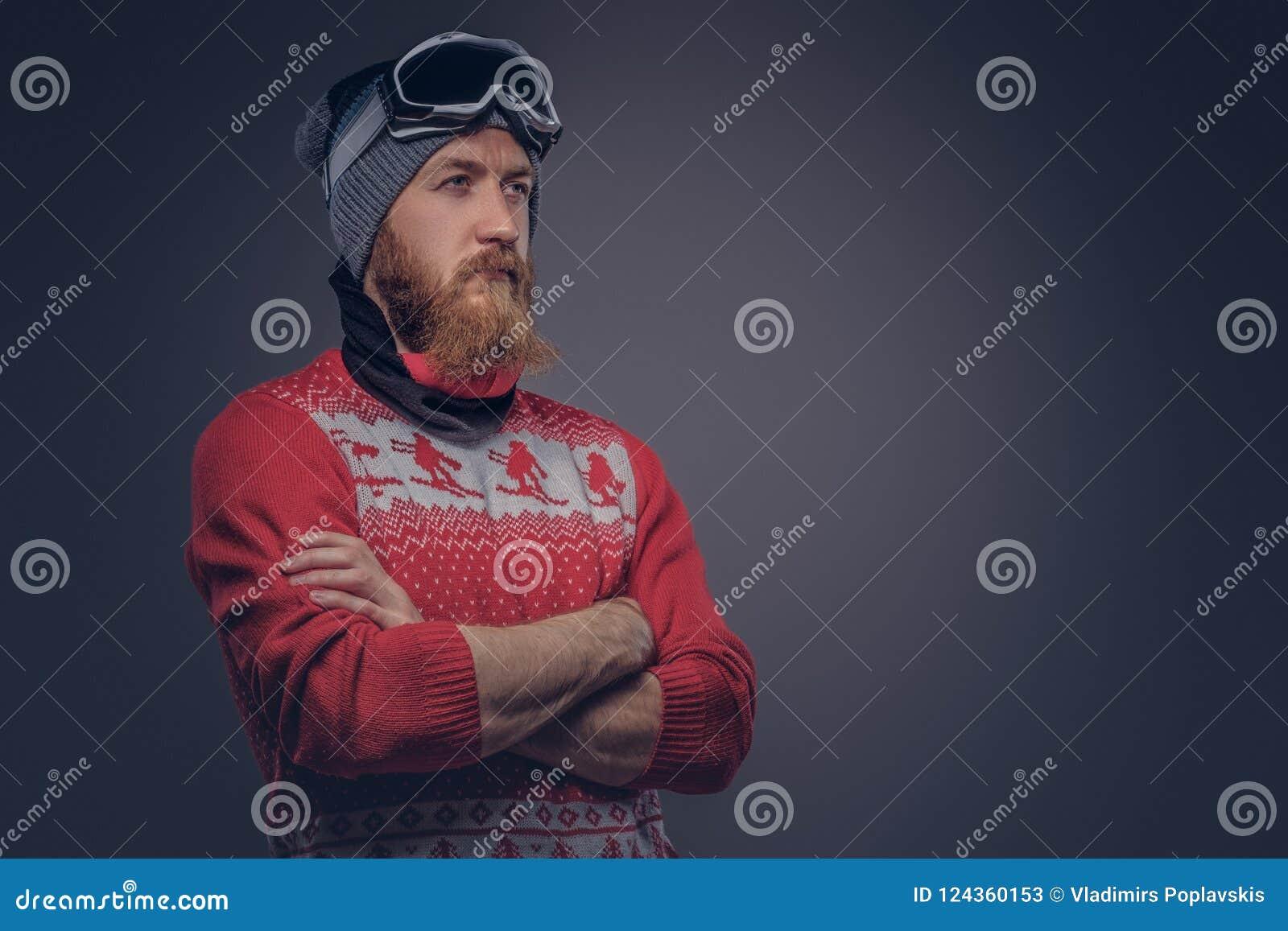 Πορτρέτο ενός βάναυσου redhead γενειοφόρου αρσενικού σε ένα χειμερινό καπέλο με τα προστατευτικά γυαλιά που ντύνονται σε ένα κόκκ