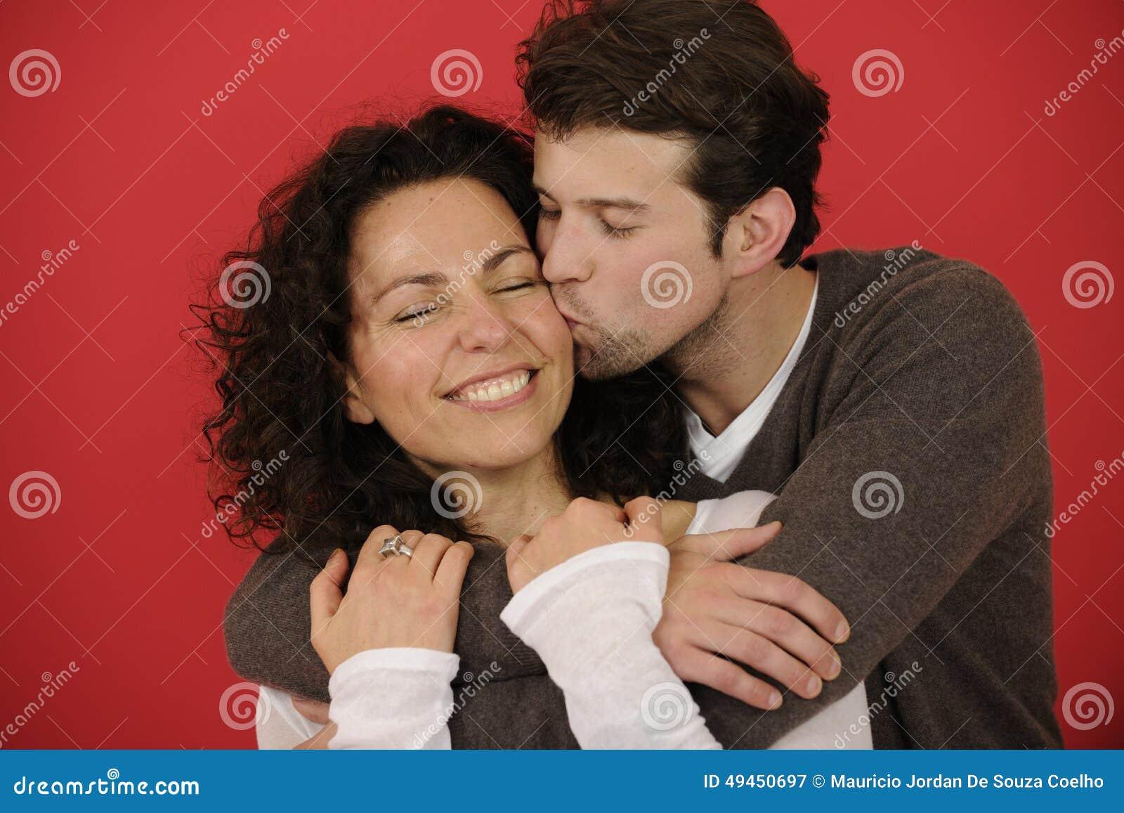 Πορτρέτο ενός ευτυχούς ζεύγους στο κόκκινο υπόβαθρο