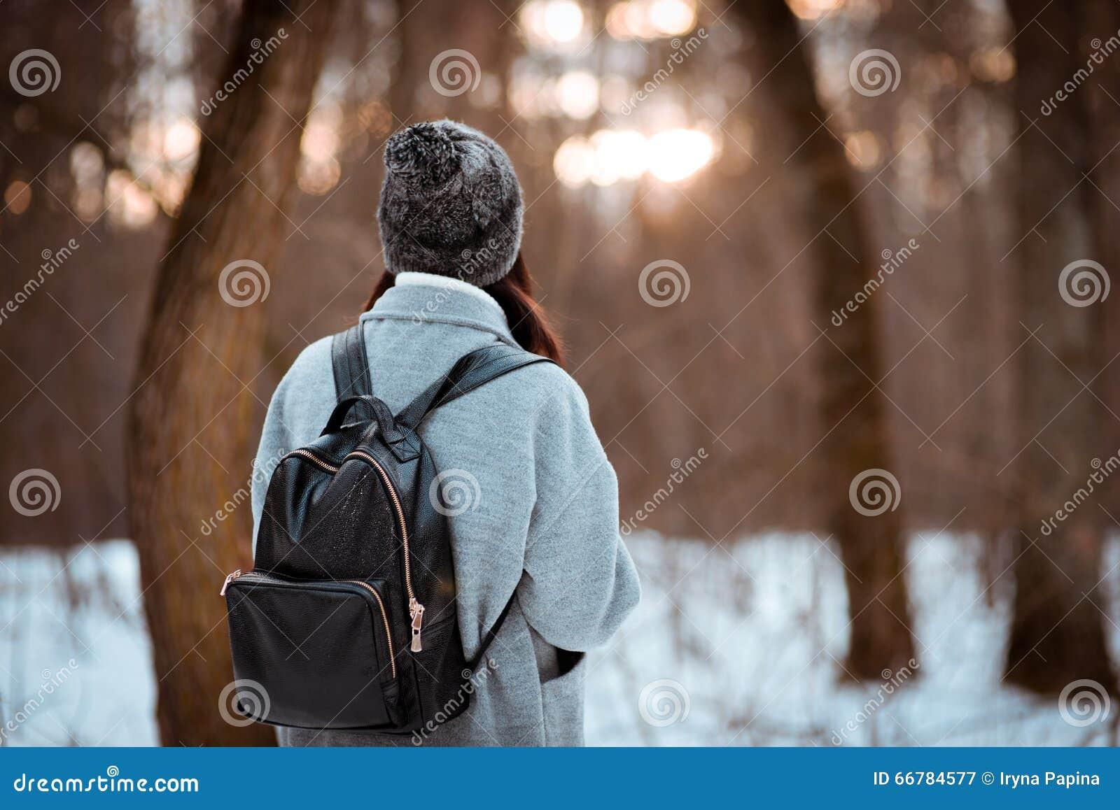 Πορτρέτο ενός ευτυχούς όμορφου κοριτσιού με την καφετιά τρίχα στο χειμερινό δάσος που ντύνεται σε ένα ύφος hipster, τρόπος ζωής