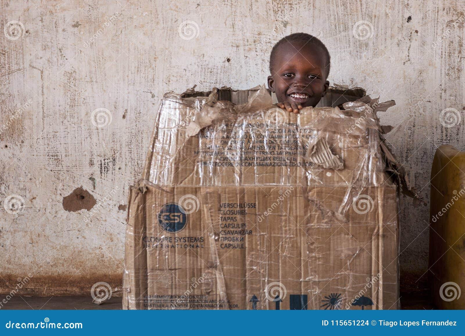 Πορτρέτο ενός νέου αγοριού που παίζει σε ένα κιβώτιο καρτών στην πόλη Nhacra στη Γουινέα-Μπισσάου