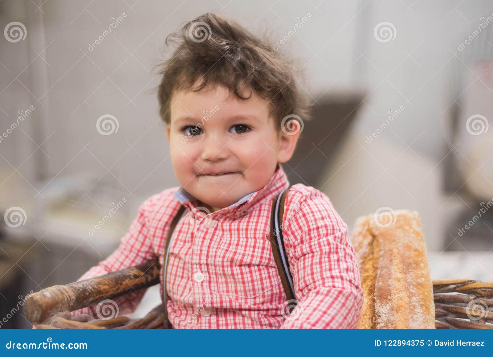 Πορτρέτο ενός χαριτωμένου μωρού μέσα σε ένα καλάθι με το ψωμί στο αρτοποιείο