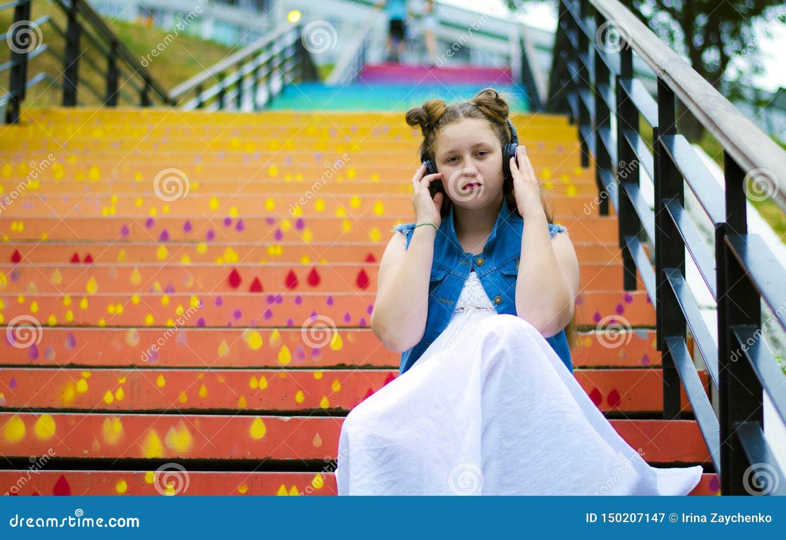 Πορτρέτο ενός όμορφου, νέο κορίτσι που κάθεται στα σκαλοπάτια και ακούει τη μουσική στα ακουστικά, στην οδό, το καλοκαίρι