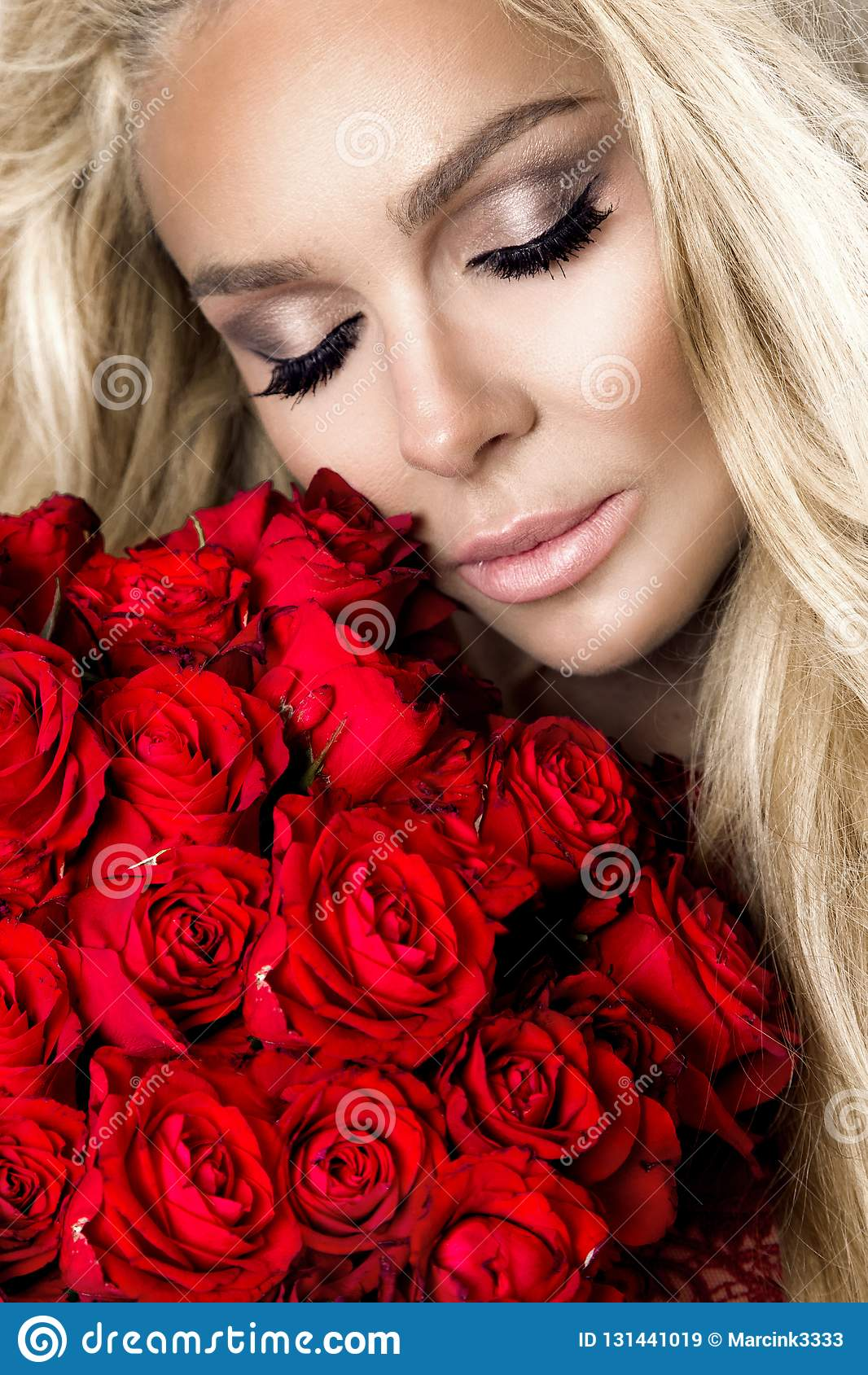 Πορτρέτο ενός όμορφου ξανθού θηλυκού προτύπου με τη μακριά, όμορφη τρίχα Πρότυπο προκλητικό lingerie, που κρατά τα κόκκινα τριαντ