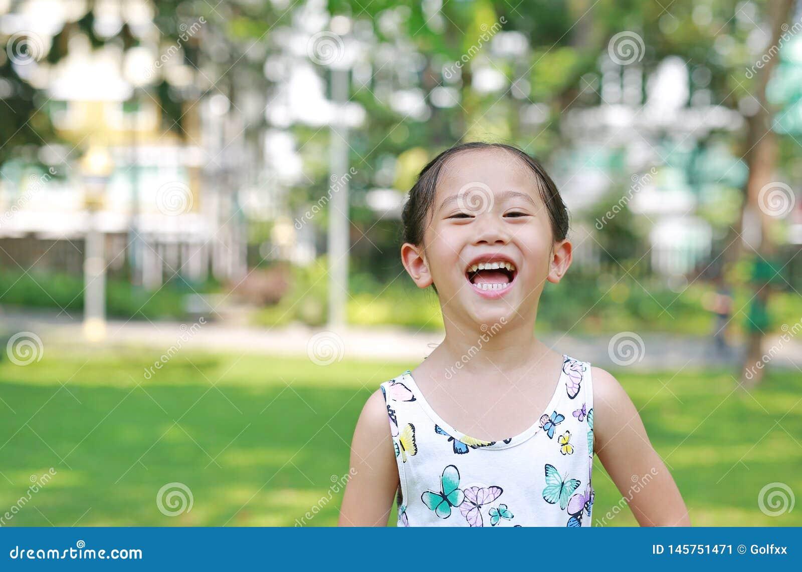 Πορτρέτο ευτυχούς λίγο ασιατικό κορίτσι παιδιών στο ηλιόλουστο πράσινο πάρκο