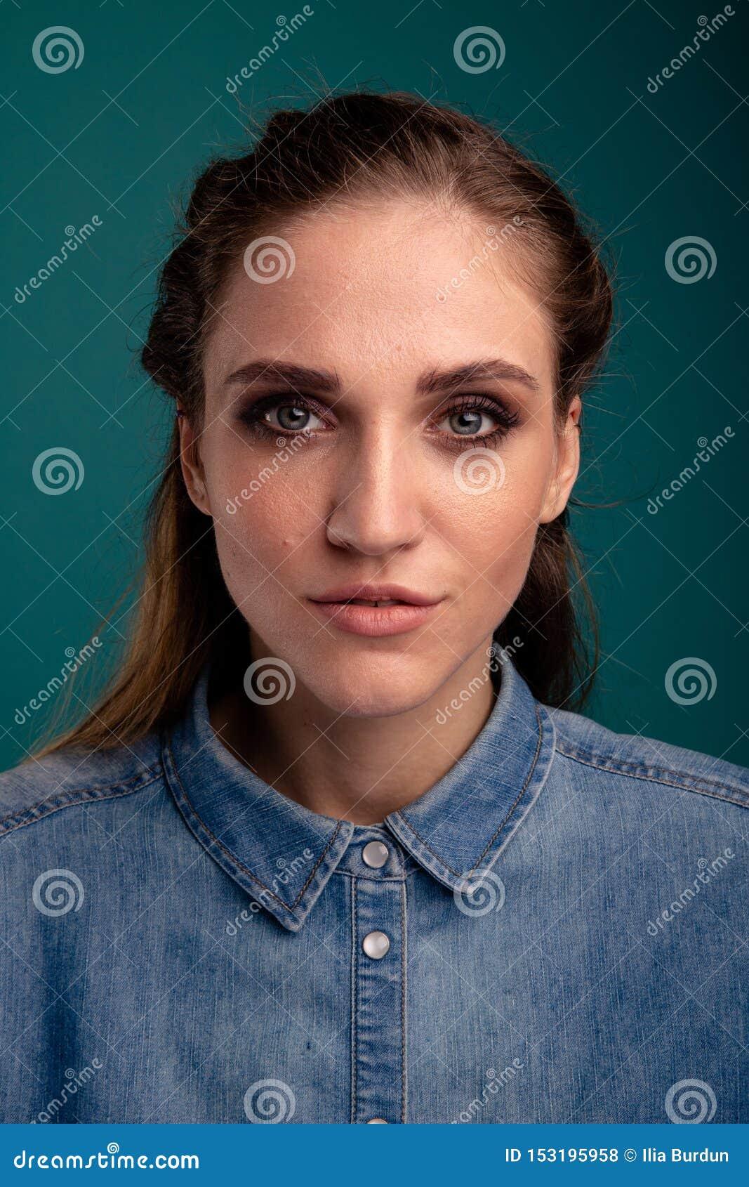 Πορτρέτο κινηματογραφήσεων σε πρώτο πλάνο της αρκετά νέας τοποθέτησης γυναικών σε ένα στούντιο που απομονώνεται πέρα από το μπλε