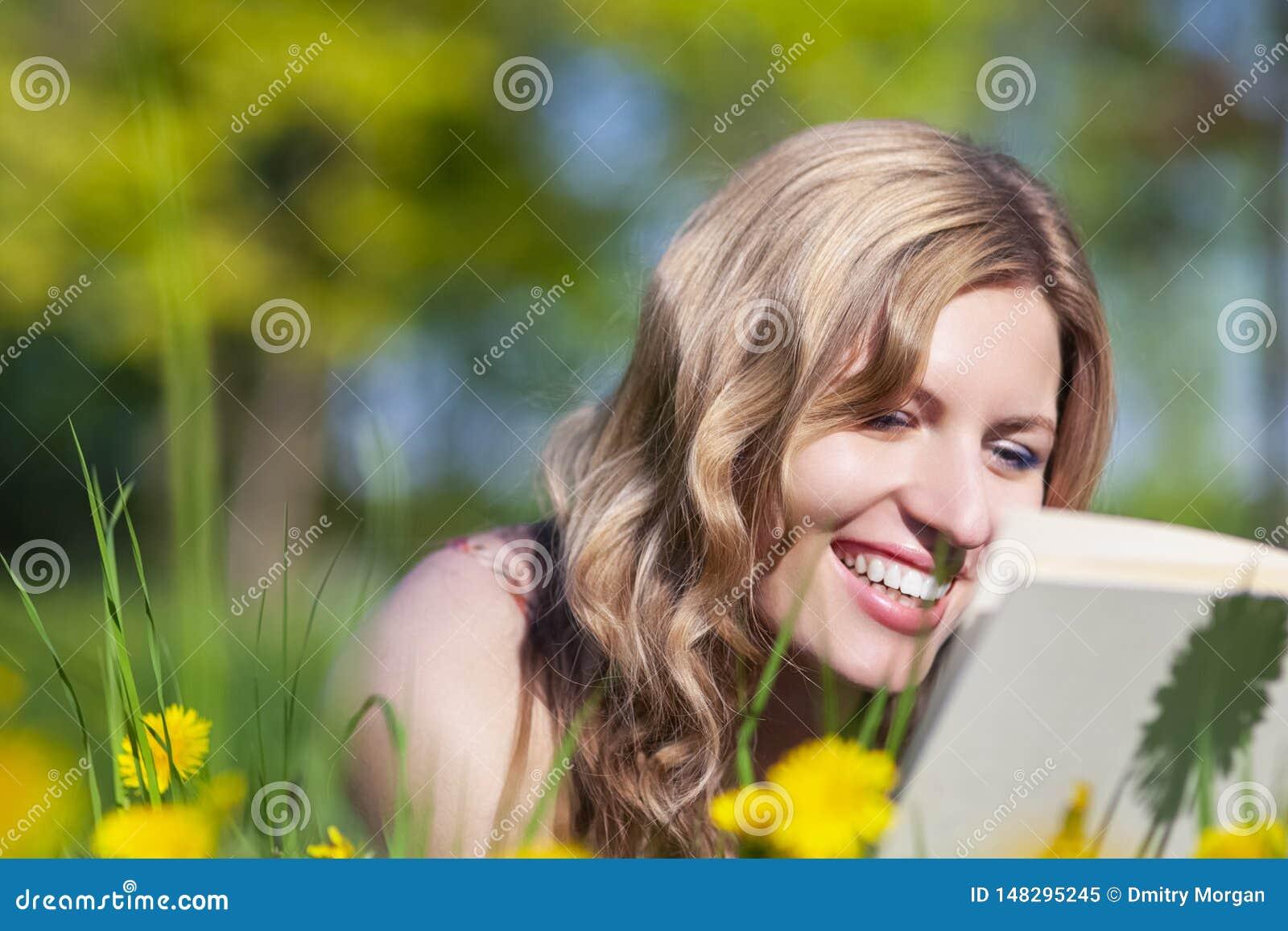 Πορτρέτο κινηματογραφήσεων σε πρώτο πλάνο του ευτυχούς χαμογελώντας καυκάσιου θηλυκού με το βιβλίο που βρίσκεται και που διαβάζει