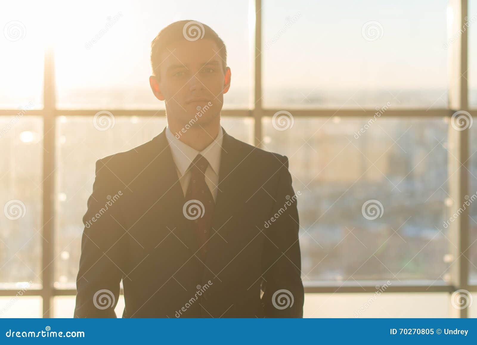Πορτρέτο κινηματογραφήσεων σε πρώτο πλάνο ενός νέου όμορφου επιχειρηματία, που εξετάζει σοβαρά τη κάμερα, που στέκεται στο ελαφρύ