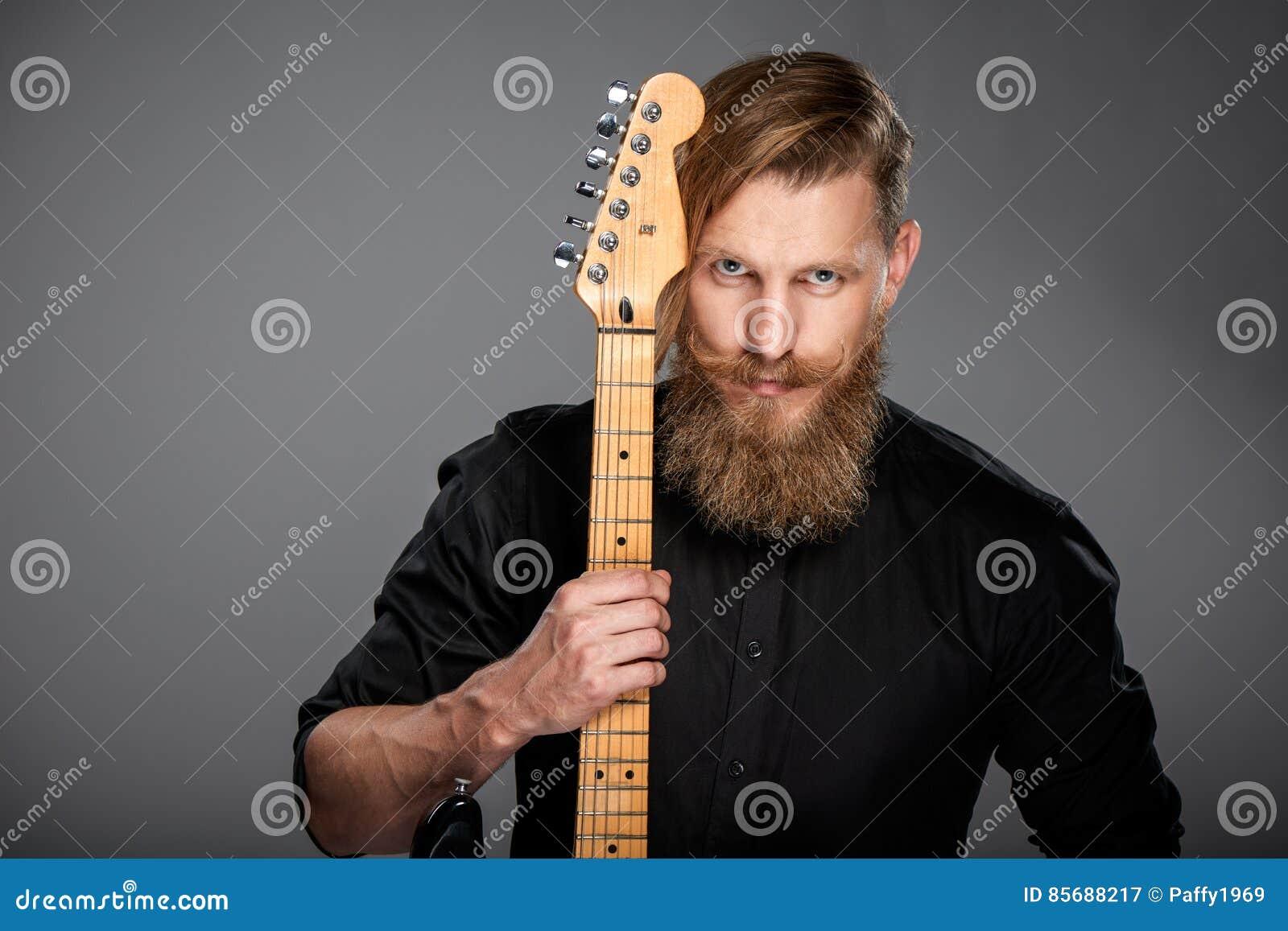Πορτρέτο κινηματογραφήσεων σε πρώτο πλάνο του ατόμου hipster με την κιθάρα