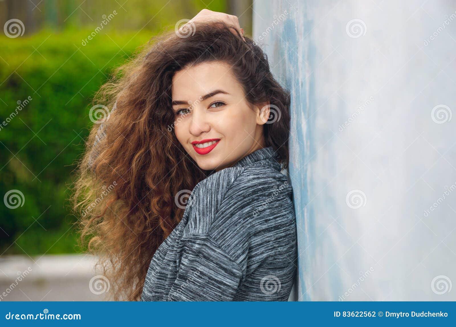 Πορτρέτο μιας ελκυστικής νέας γυναίκας με τη σγουρή τρίχα που στέκεται με την πίσω στον τοίχο