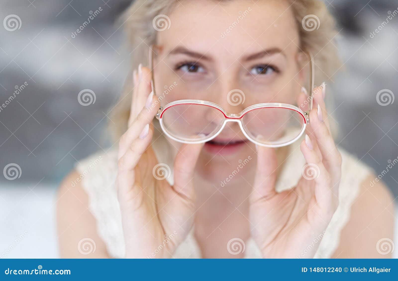 Πορτρέτο μιας νέας γυναίκας με τα γυαλιά και των ξανθών μαλλιών που κρατά τα γυαλιά μπροστά από το πρόσωπό της, το πρόσωπό της απ