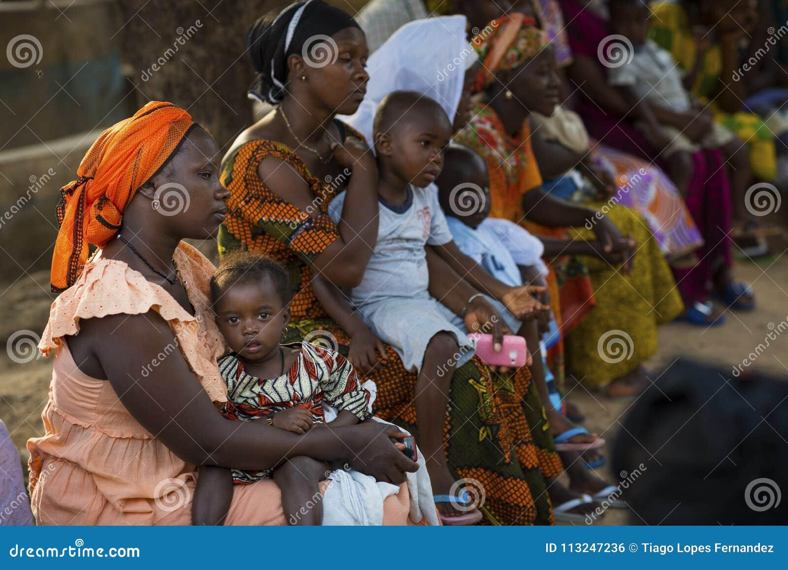 Πορτρέτο μιας νέας μητέρας και της κόρης μωρών της κατά τη διάρκεια μιας κοινοτικής συνεδρίασης, στη γειτονιά Bissaque στην πόλη