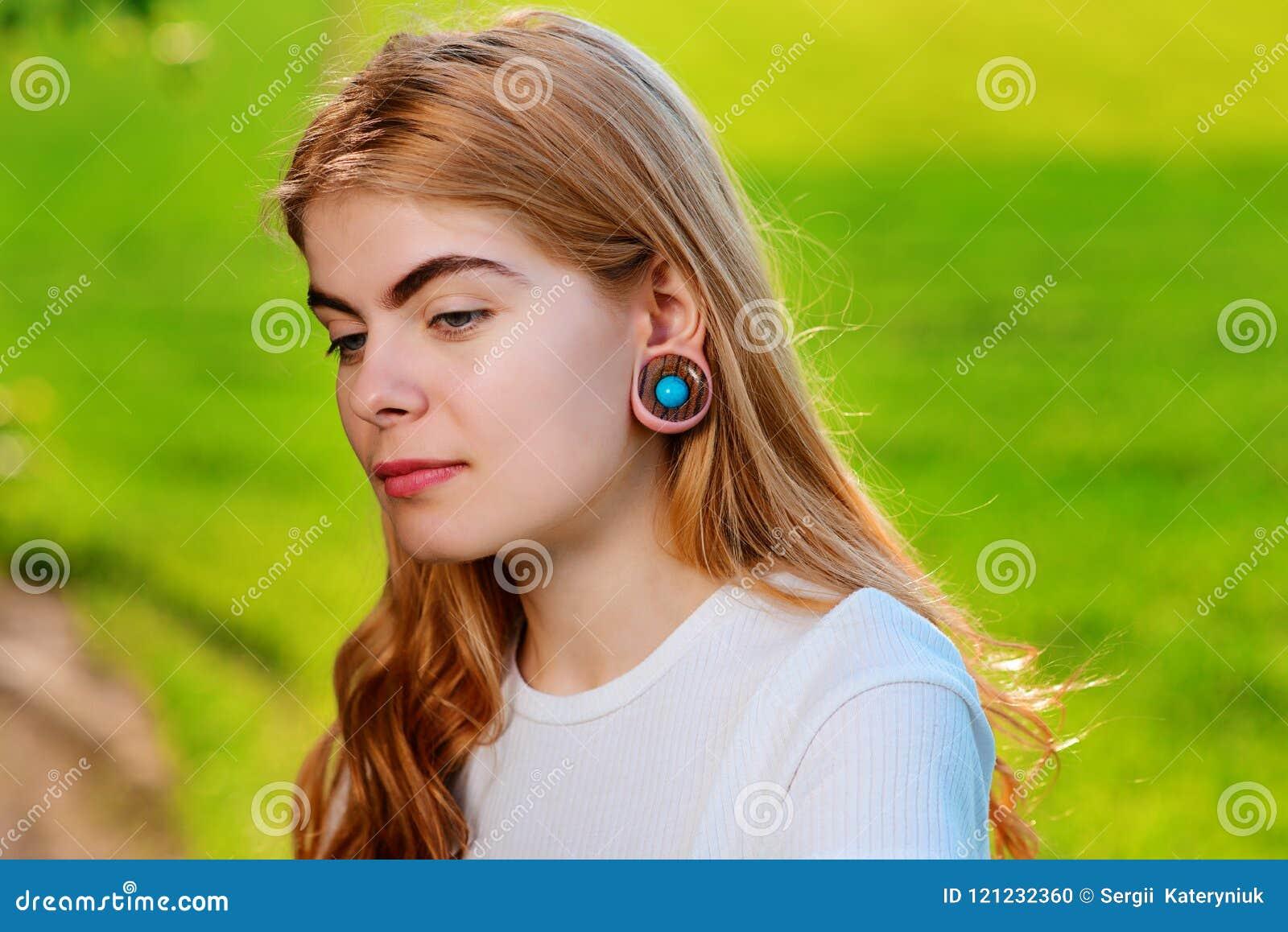 Πορτρέτο μιας νέας όμορφης γυναίκας με τις ξύλινες σήραγγες στο ε της