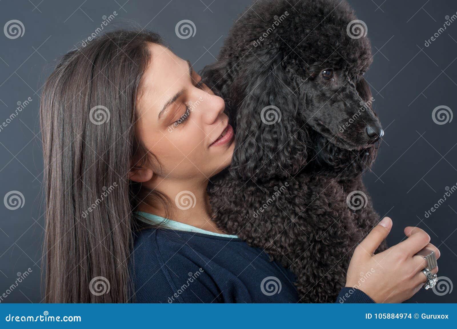Πορτρέτο μιας όμορφης νέας γυναίκας που αγκαλιάζει το όμορφο σκυλί της