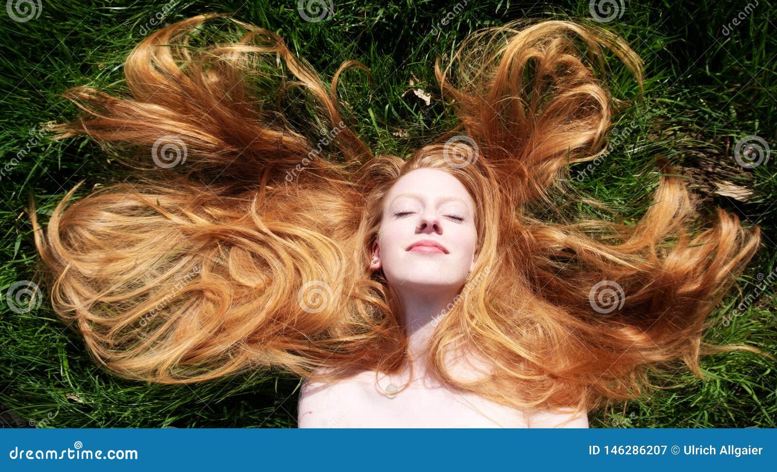 Πορτρέτο μιας όμορφης νέας προκλητικής κοκκινομάλλους γυναίκας, που βρίσκεται την άνοιξη ήλιος, που χαλαρώνει στην πράσινη χλόη,