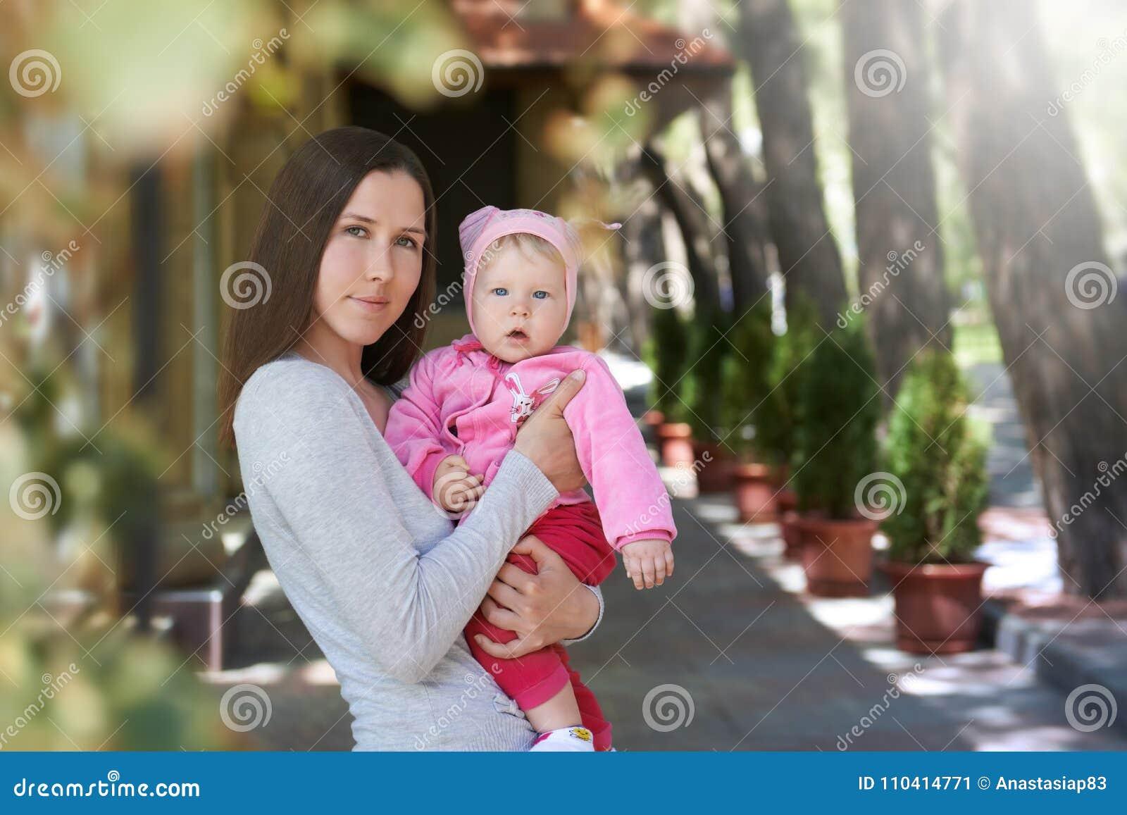 Πορτρέτο οδών της νέας μητέρας που αγκαλιάζει την κόρη της με την αγάπη