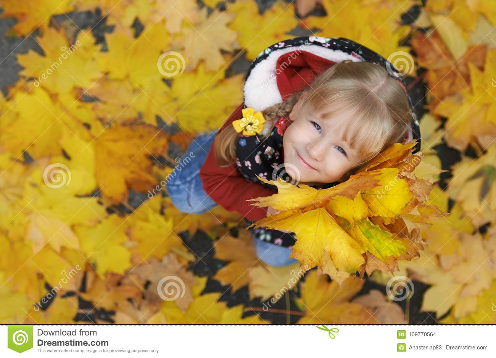 Πορτρέτο οδών φθινοπώρου του μικρού κοριτσιού που κρατά μια δέσμη των φύλλων σφενδάμου
