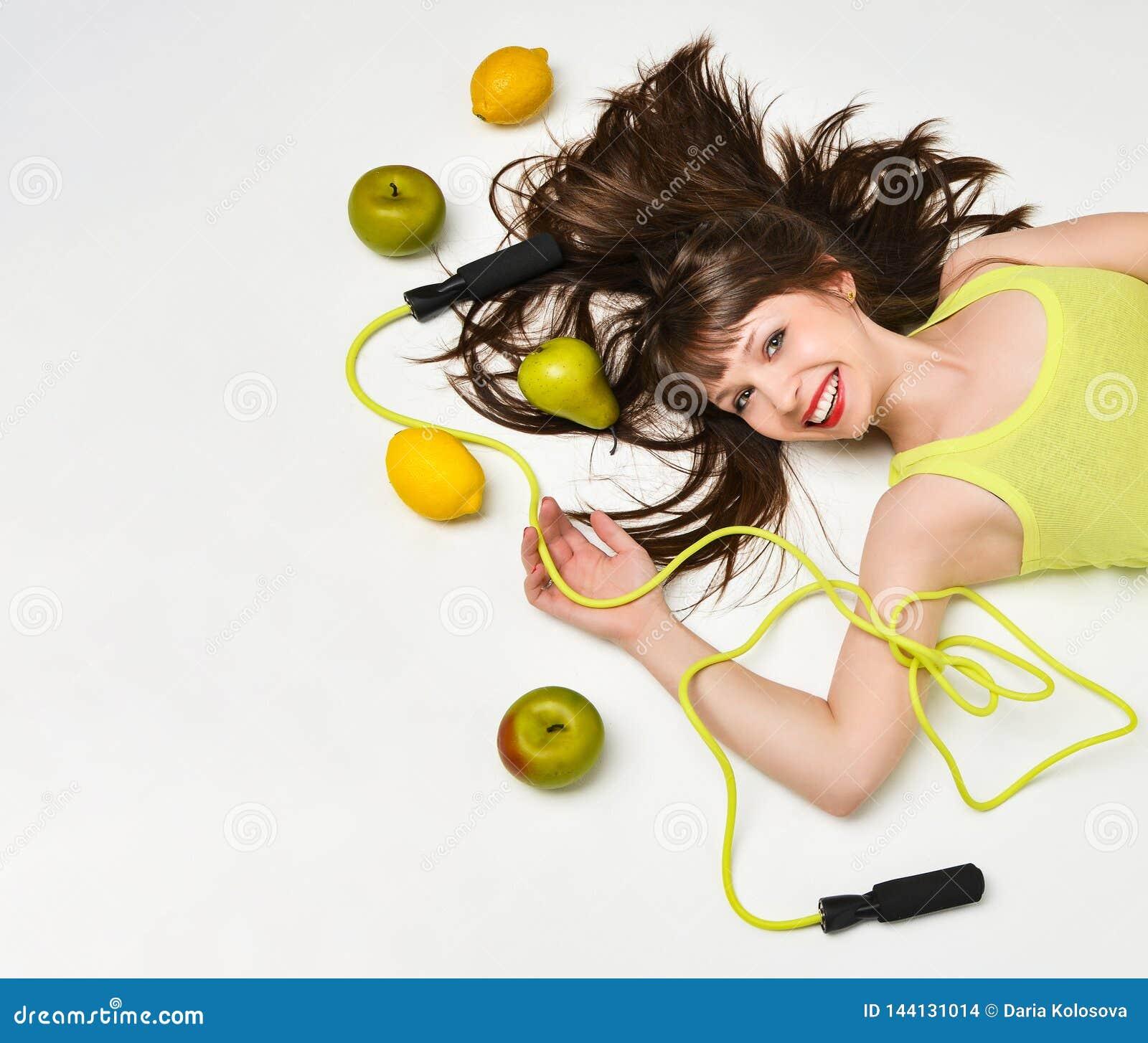 Πορτρέτο ομορφιάς μιας γυναίκας που περιβάλλονται από τα φρούτα και ενός πηδώντας σχοινιού που βρίσκεται στο πάτωμα
