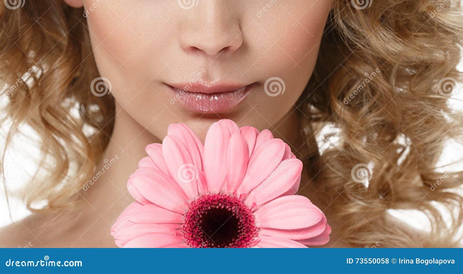 Πορτρέτο ομορφιάς πηγουνιών χειλικής μύτης γυναικών με το λουλούδι στα σγουρά ξανθά μαλλιά τρίχας