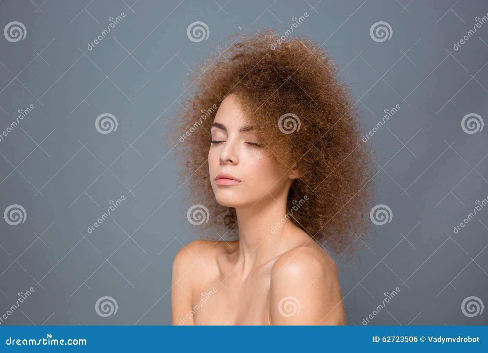 Πορτρέτο ομορφιάς της νέας φυσικής γυναίκας με το ογκώδες σγουρό hairstyle