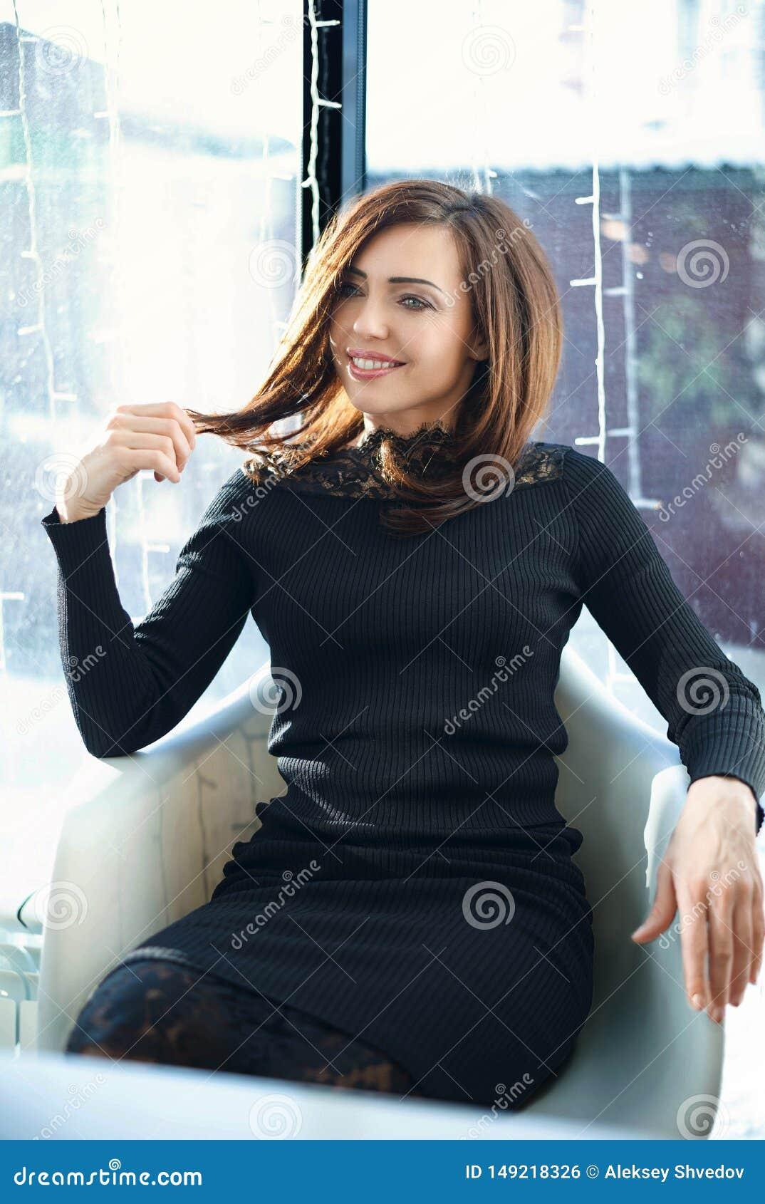Πορτρέτο που γοητεύει τη νέα γυναίκα με το φιλικό χαμόγελο, μακρύς καφές χαμόγελου τρίχας brunette