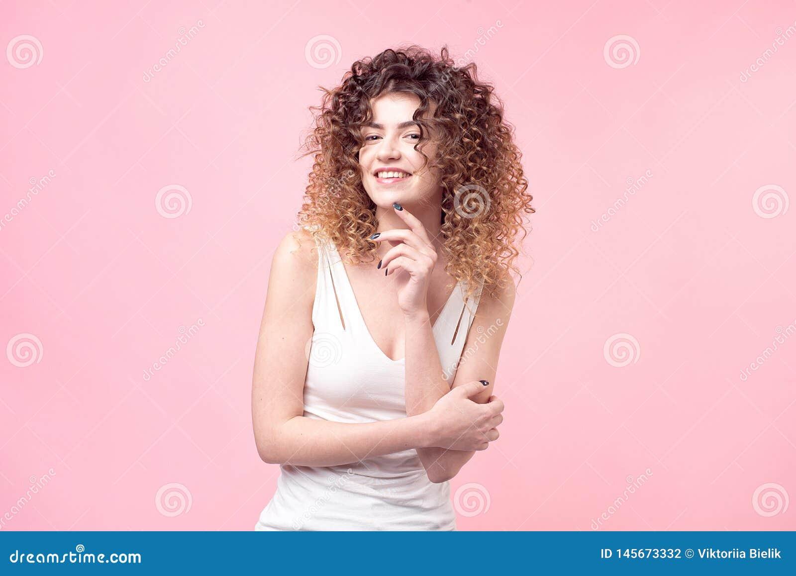 Πορτρέτο στούντιο μόδας της όμορφης χαμογελώντας γυναίκας με τις μπούκλες afro hairstyle που απομονώνεται πέρα από το ρόδινο υπόβ