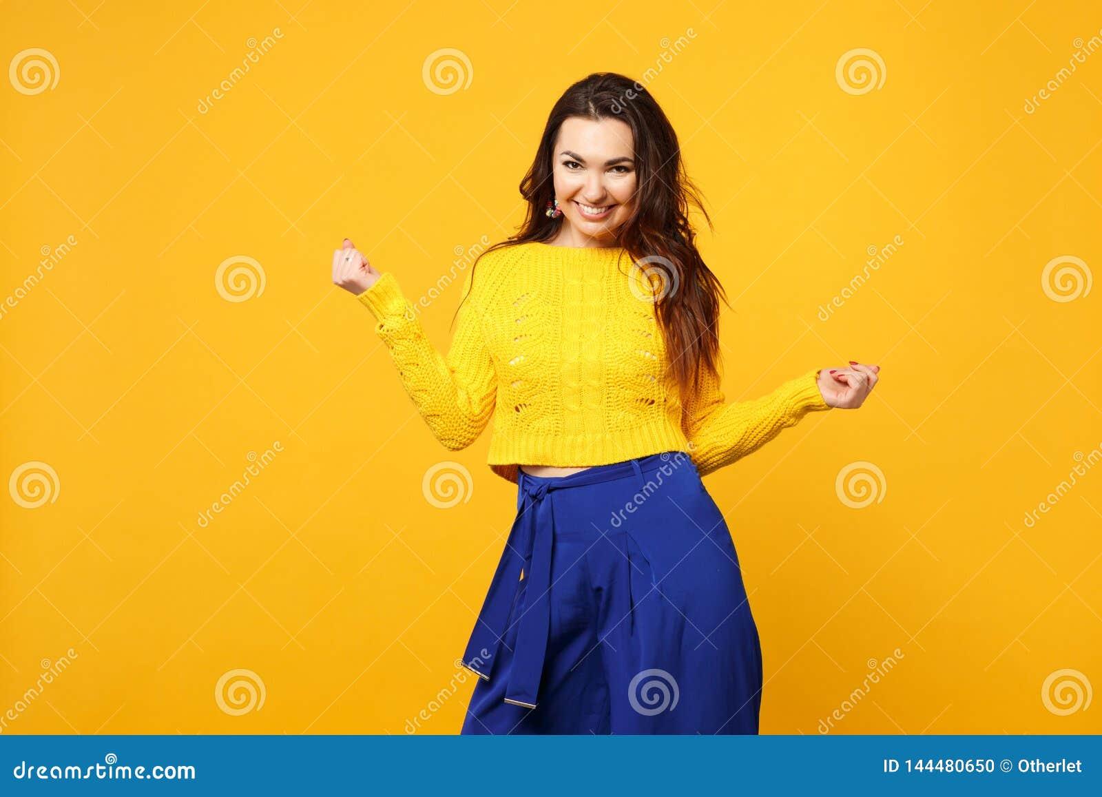 Πορτρέτο της αρκετά νέας γυναίκας στο πουλόβερ, μπλε παντελόνι που φαίνεται κάμερα, χέρια διάδοσης που απομονώνονται στο κίτρινο
