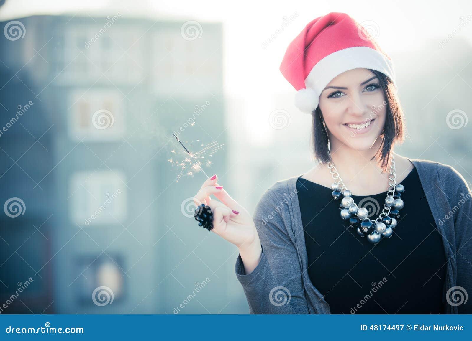 Πορτρέτο της ευτυχούς γυναίκας που κρατά τα φω τα της Βεγγάλης πέρα από το υπόβαθρο πόλεων Γυναίκα Χριστουγέννων με το sparkler Π