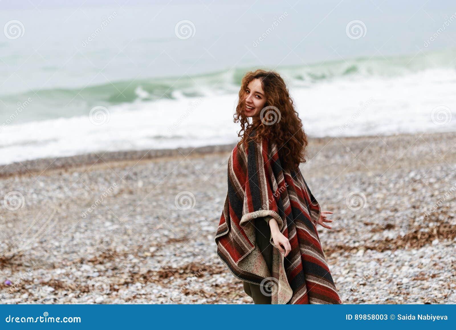 Πορτρέτο της ευτυχούς γυναίκας brunette στην παραλία που φορά poncho