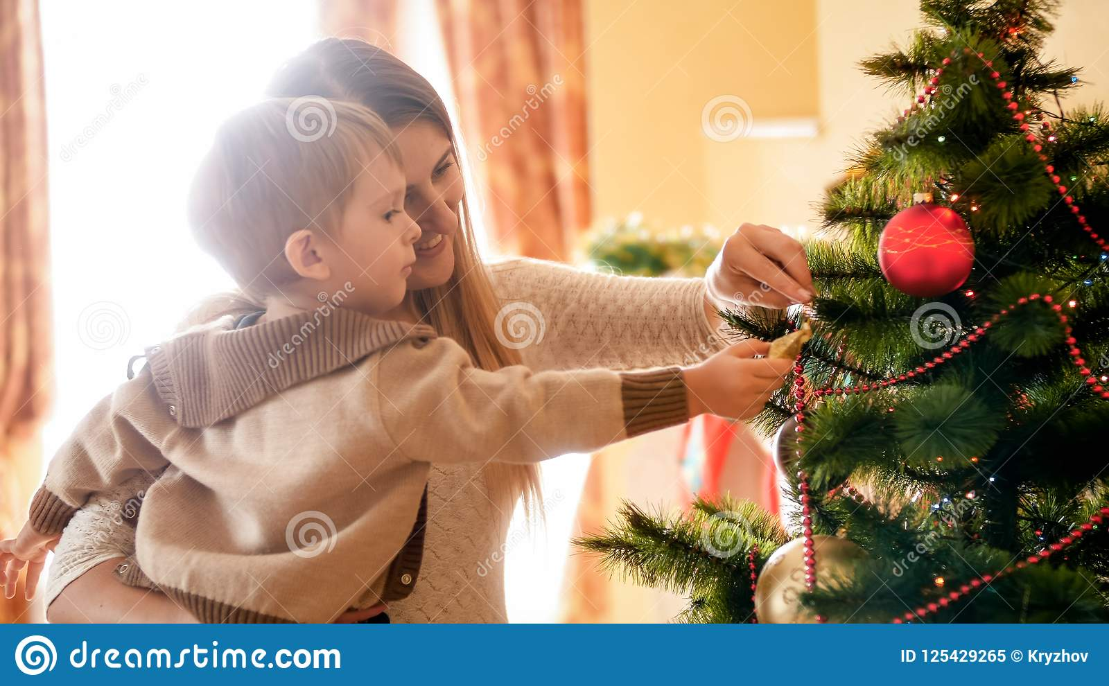 Πορτρέτο της ευτυχούς χαμογελώντας μητέρας με το decroating χριστουγεννιάτικο δέντρο παιδιών της στο πρωί