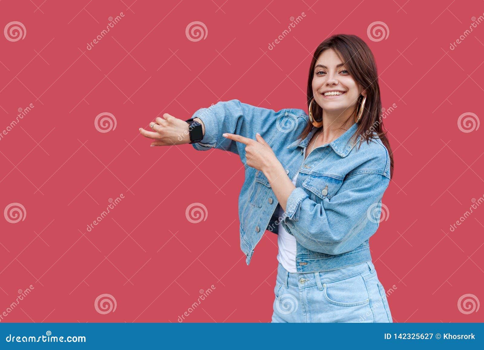 Πορτρέτο της ευτυχούς όμορφης νέας γυναίκας brunette με το makeup μόνιμη παρουσίαση ύφους τζιν στην περιστασιακή και την υπόδειξη