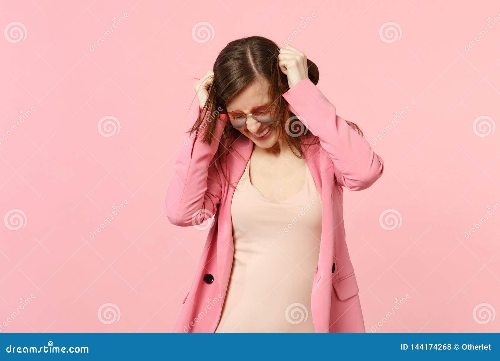 Πορτρέτο της εύθυμης αρκετά νέας γυναίκας στα γυαλιά καρδιών με το χαμηλωμένο κεφάλι που κρατά τα χέρια στην τρίχα στο ροζ κρητιδ