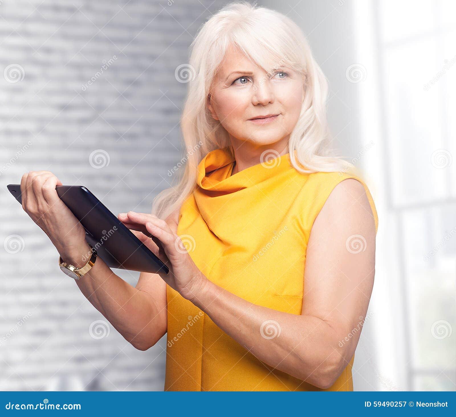 Πορτρέτο της ελκυστικής ανώτερης επιχειρηματία που χρησιμοποιεί την ταμπλέτα
