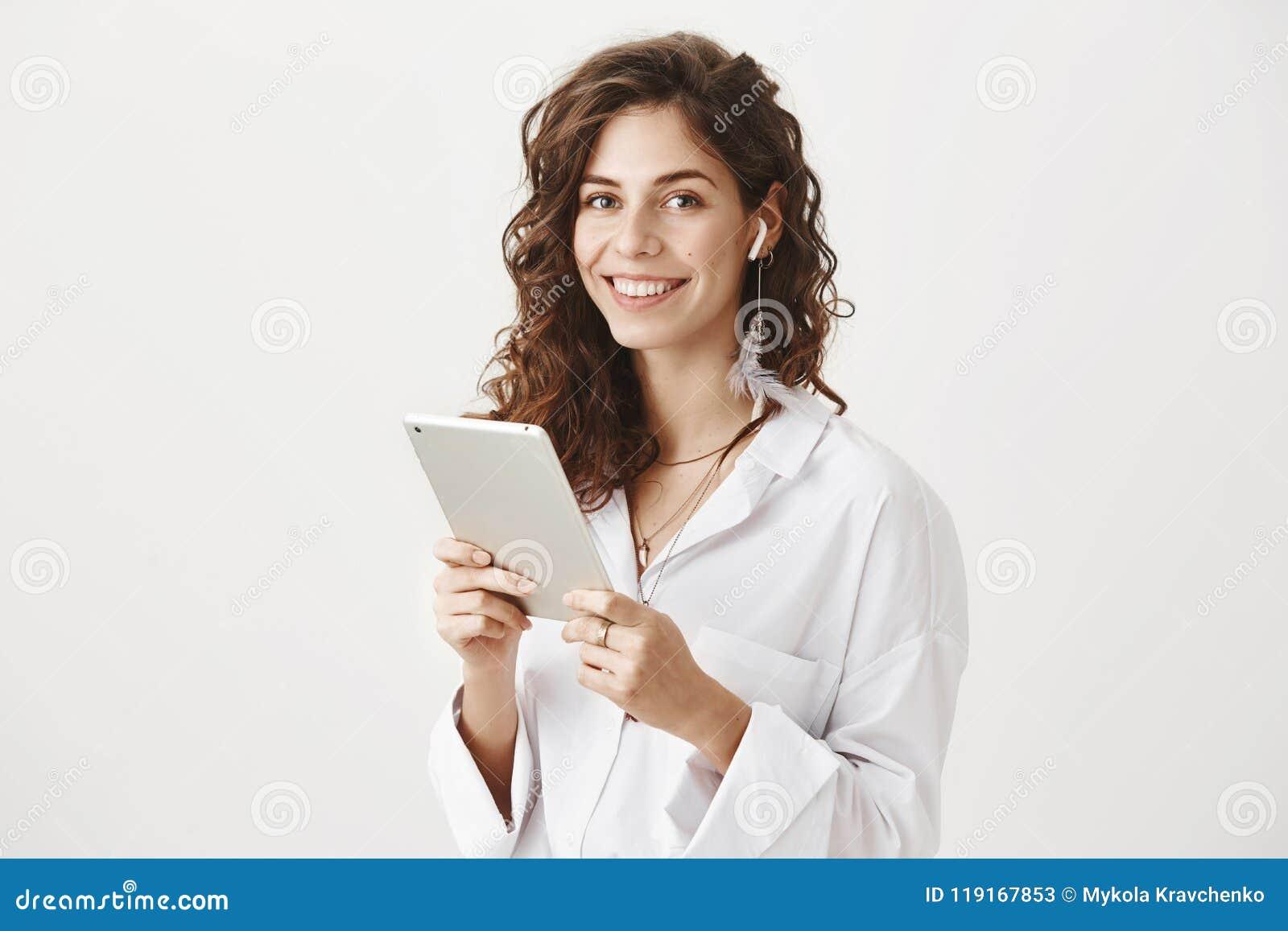 Πορτρέτο της θετικής και επιτυχούς καυκάσιας θηλυκής ταμπλέτας εκμετάλλευσης, μουσική ακούσματος στα ασύρματα earbuds, χαμόγελο