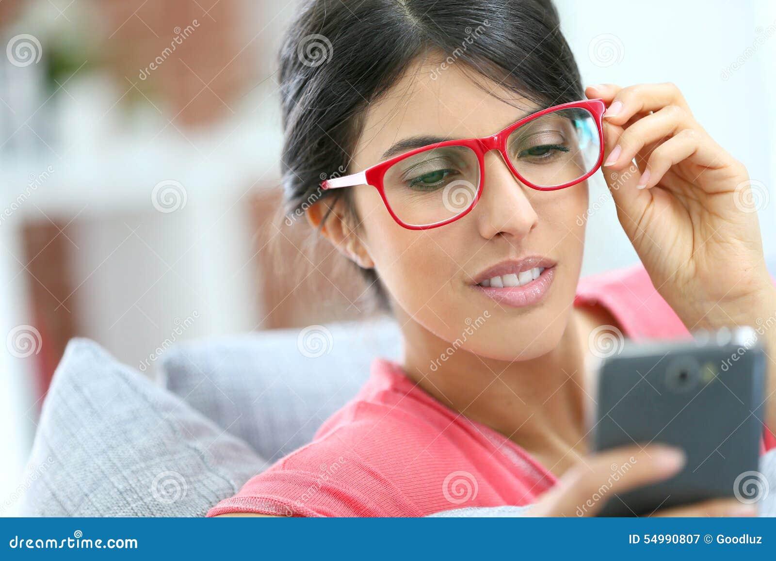 Πορτρέτο της κομψής νέας γυναίκας που χρησιμοποιεί το smartphone
