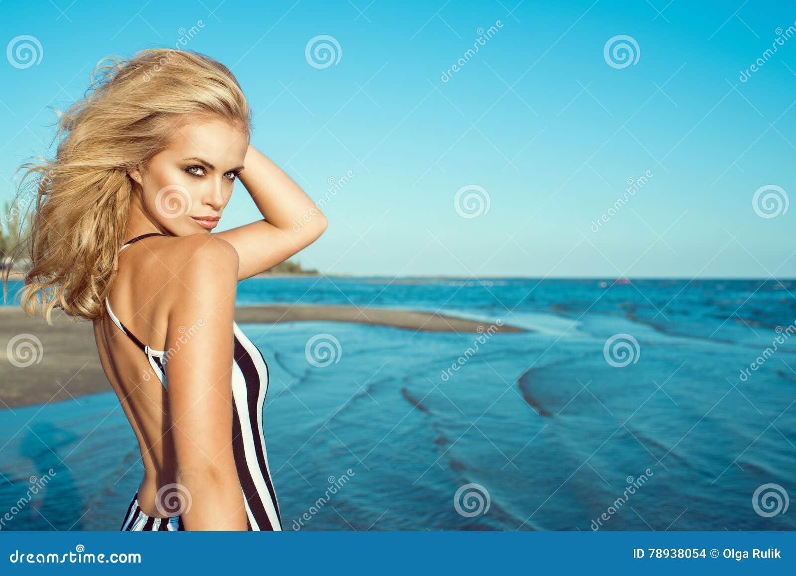 Πορτρέτο της κομψής ξανθής γυναίκας στο ριγωτό φόρεμα με τη γυμνή πίσω στάση στην παραλία και να φανεί ευθύς