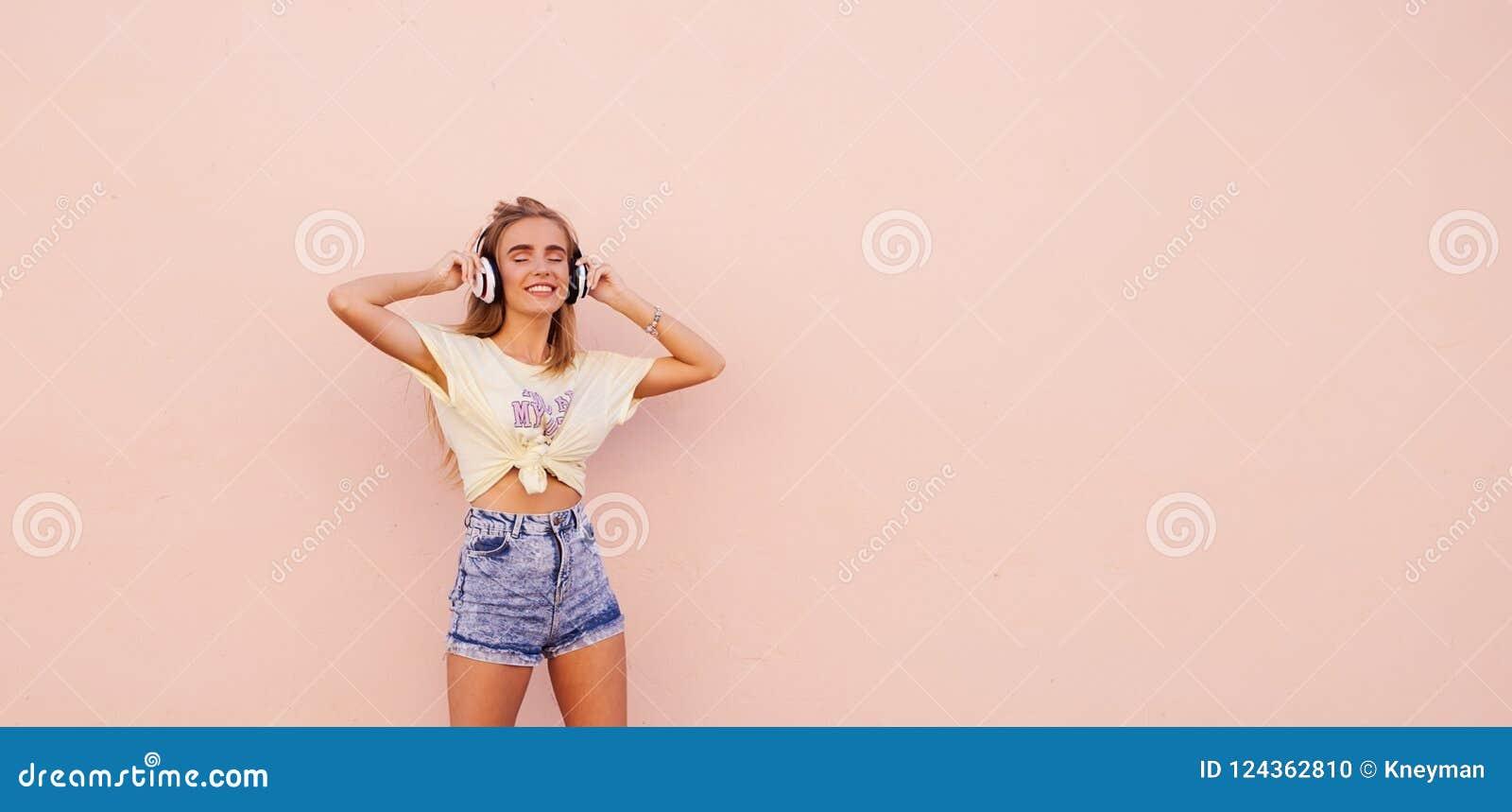 Πορτρέτο της μόδας ομορφιάς που χαμογελά τις νέες γυναίκες με τα κίτρινα γυαλιά ηλίου, τα ασύρματα ακουστικά, το χορό και τη χαλά