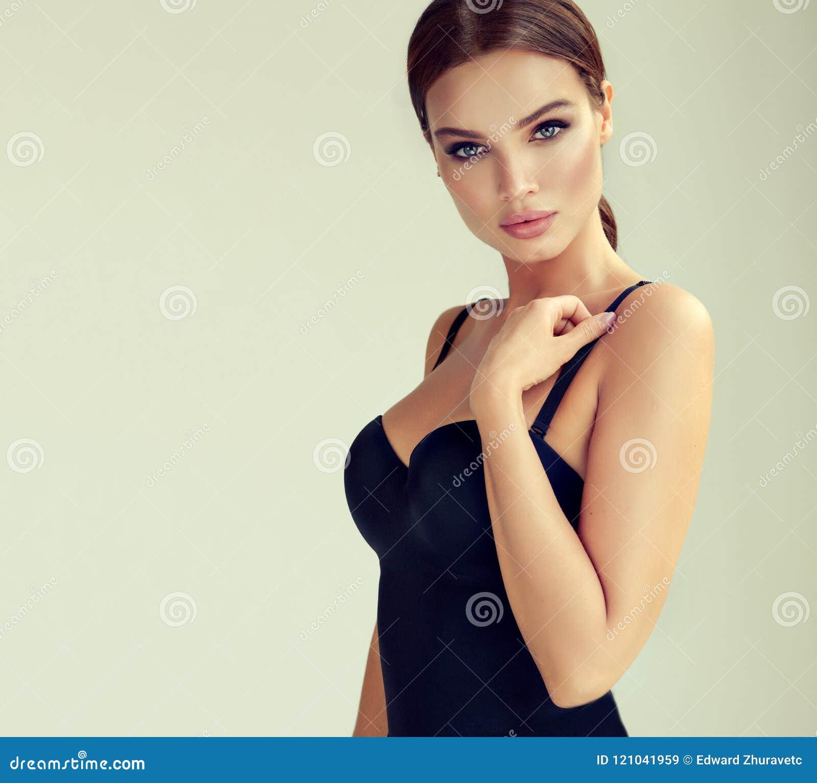 Πορτρέτο της νέας, σεξουαλικής γυναίκας που ντύνεται στο σαγηνευτικό μαύρο σώμα Makeup και cosmetology