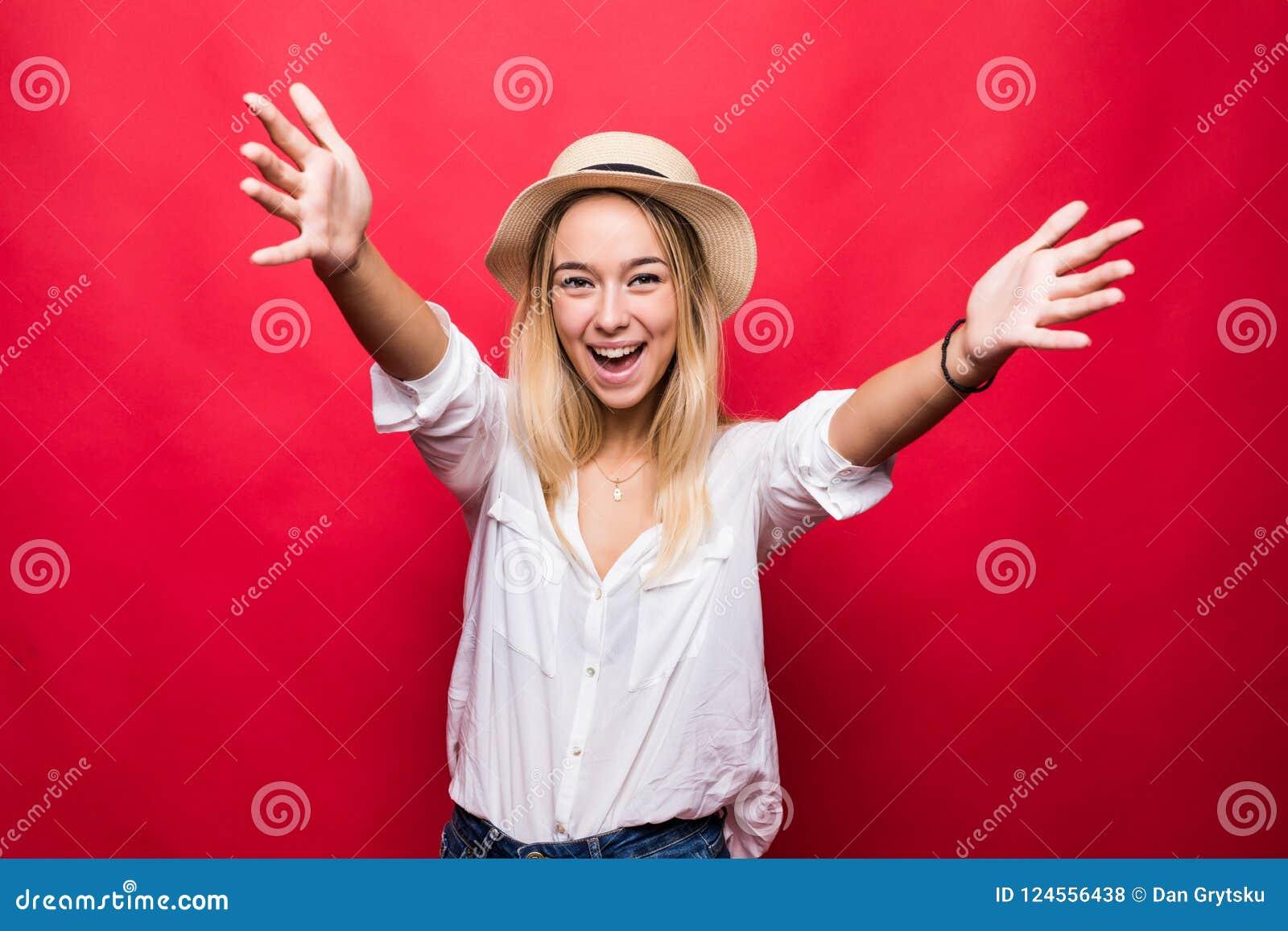 Πορτρέτο της νέας όμορφης γυναίκας στο καπέλο αχύρου με τους ανοικτούς φοίνικες, που απομονώνεται στο κόκκινο υπόβαθρο
